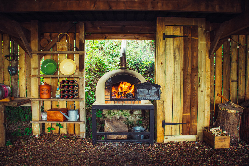 PIZZA UNDER THE STARS - One of the most popular ideas for a fun and delicious supper is to light the wood-fired oven and to practise the traditional art of pizza making in the outdoors. We can deliver seriously good ingredients straight from the restaurant so that all you need to do is roll out the dough, design your perfect pizzas using the supplied ingredients and get cooking.WHAT'S INCLUDED?(Example only - a bespoke menu can be supplied)Freshly Prepared Pizza Dough (GF dough can be provided)Homemade Tomato Sauce, Cheese, Onions, Rocket, Jalapenos,Seasonal Kitchen Garden Vegetables, Pepperoni or Ham and BasilAll pizza cooking kit is provided!£15 per person (minimum 12 people)