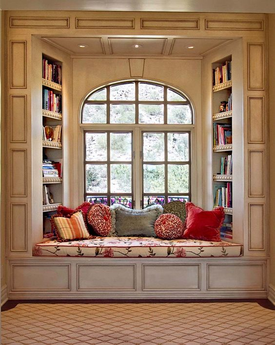 Window seat with bookshelves and throw pillows— the perfect place  to curl up with a book and a hot drink and get lost in a good book.