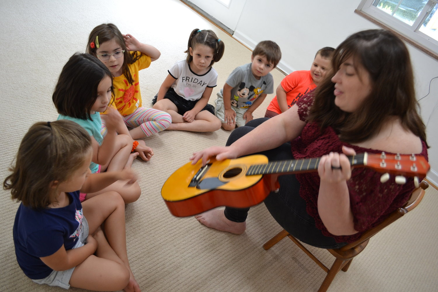 Ms. Rochelle introduces our Music Discovery campers to the guitar