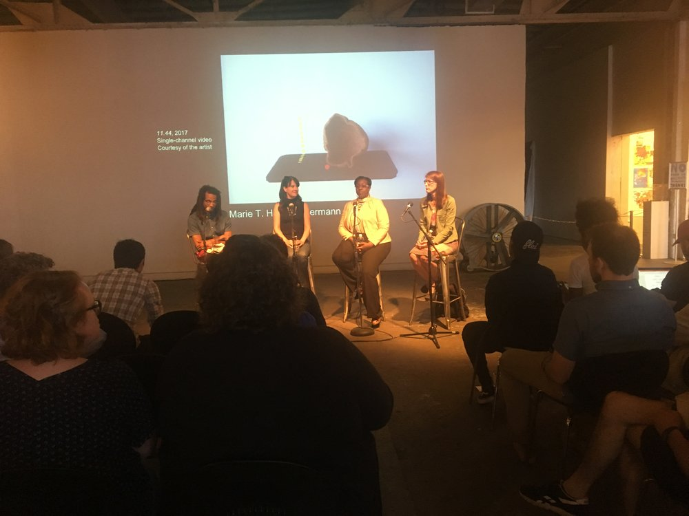 The three panelists and the moderator sitting on stools in front of an audioence at the MOCAD.
