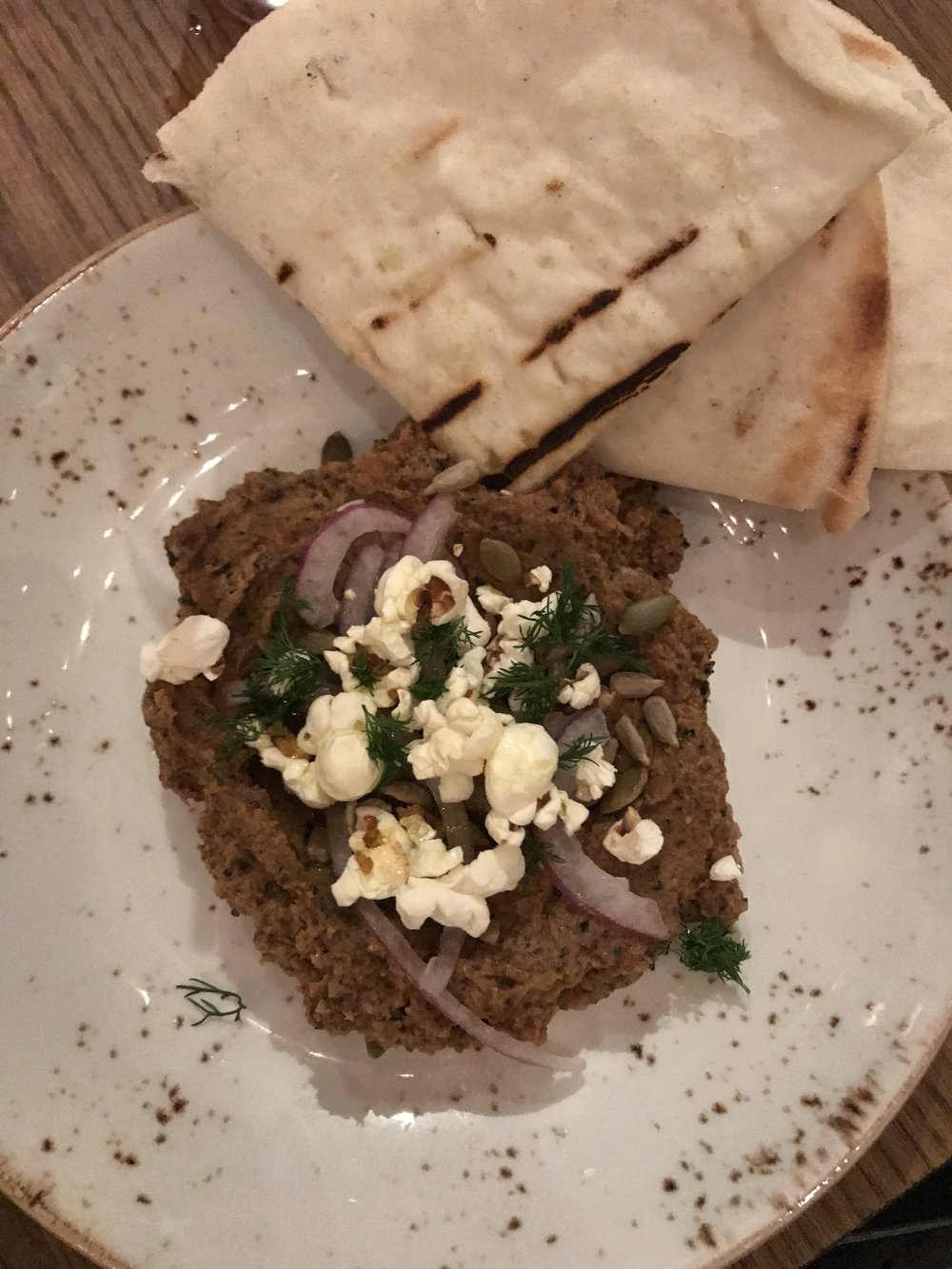 The cauliflower hummus at The Little Beet Table is served with gluten free pita and is topped with red onion, dill, popped sorghum, sunflower seeds and pumpkin seeds for added crunch.