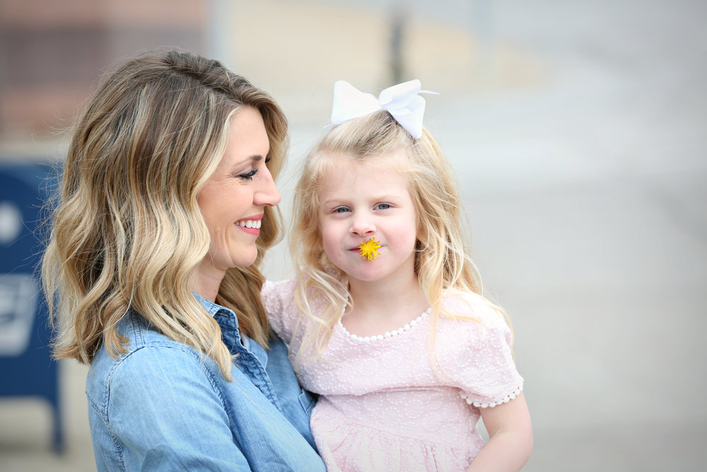 Fashion blogger, Lady and Red holding daughter, R who has a dandelion in her mouth. | LadyandRed.com