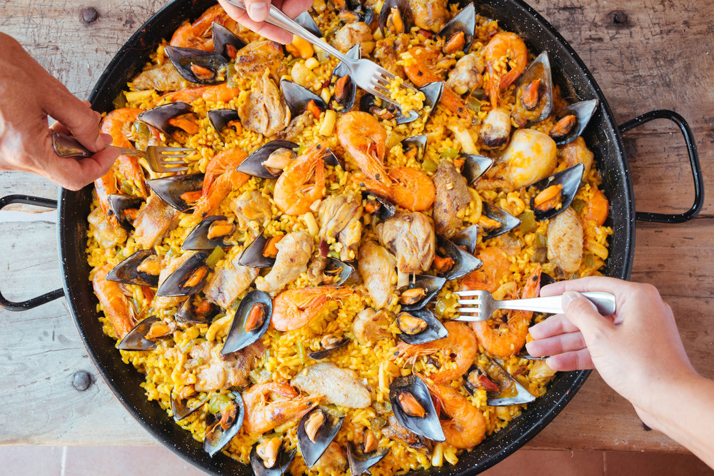 Mixed paella and hands with forks taking rice.jpg