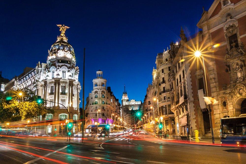 Rays of traffic lights on Gran via street, main shopping street in Madrid at night.jpg
