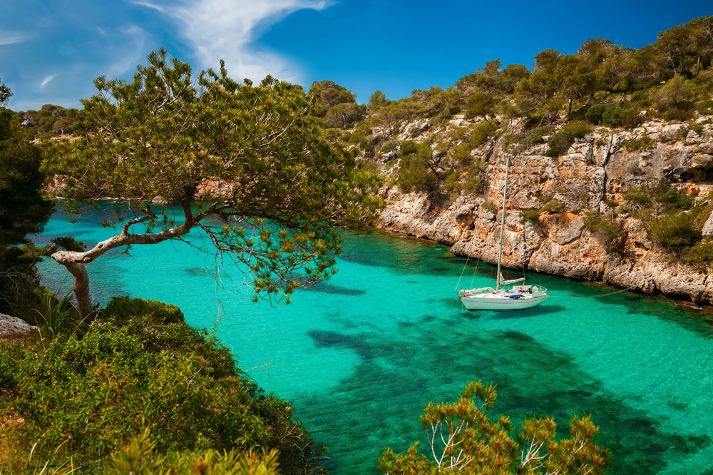 small yacht floating in azure sea in the village Cala Pi, Majorca, Spain.jpg