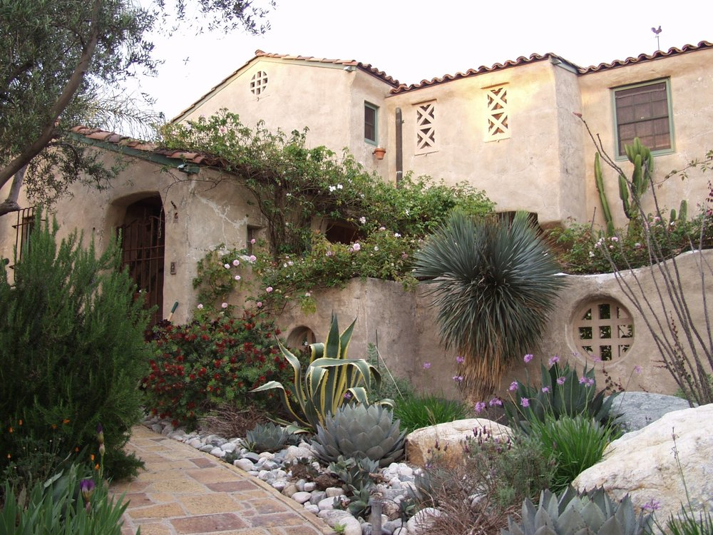 A mature olive tree was transplanted from an orchard that was being demolished in front of the entryway for privacy. A small cactus garden complete with an Ocotillo plant, a Dragon tree, variegated agaves, society garlic, and an existing dwarf bottle brush is placed at the top of the entryway stairway. All of the grass and bonsai-style podocarpus shrubs were removed to make way for the new garden.