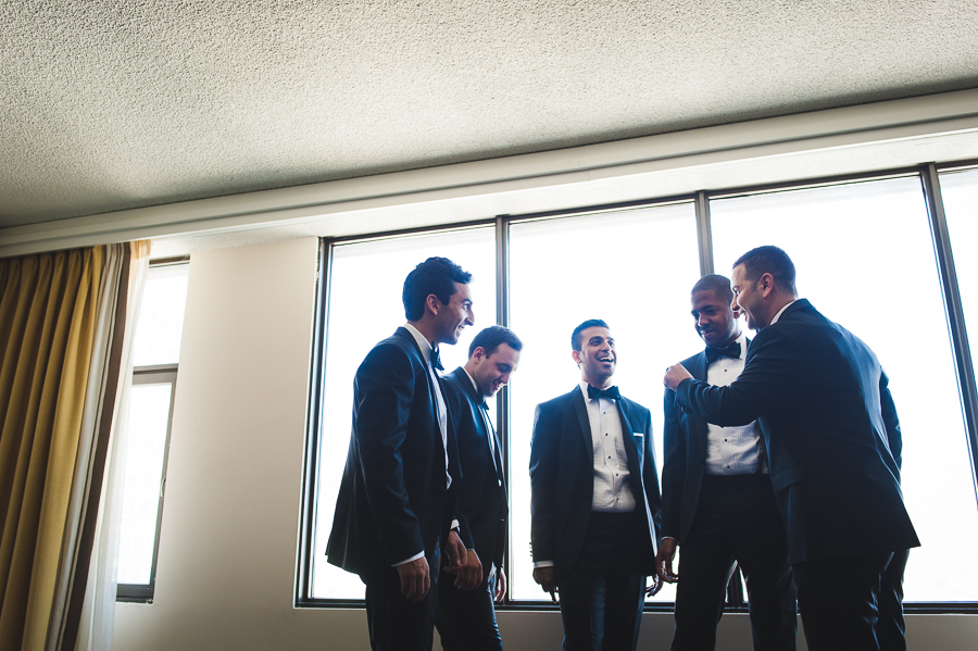 groomsmen-standing-in-circle-window-backlight