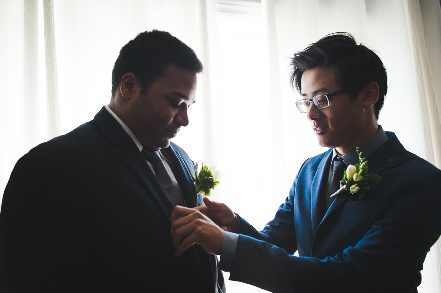 groom-boutonniere-attaching-back-light-brossard-preparing