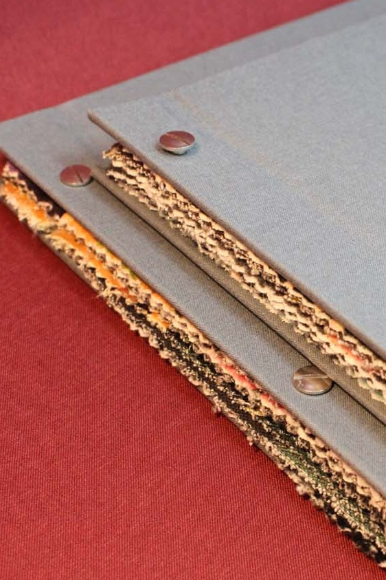 SCREWPOST - We can use screw posts to bind single pages, plastic sleeves or different materials, including fabrics. This is a good option for fabric swatch books. Screw posts can be positioned to allow the book to open along a traditional spine, or just at one corner to allow the pages to fan out.+ Long lasting+ Pages can be added or removed later+ A good method for binding non-paper materials- Doesn't open flat, so around 2.5cm is lost in the gutterMin. page count – 1Max. spine size – 10cmFile set-up – as single pages. Around 2.5cm will be lost in the gutter, so you'll need to account for this in the book design.