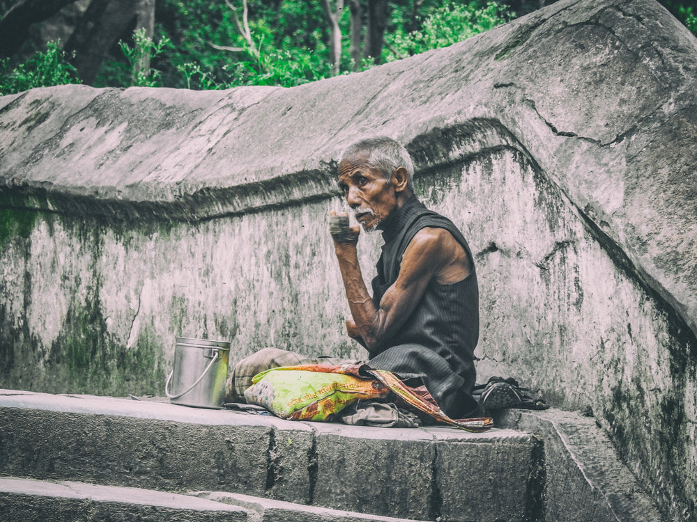 A beggar sits at the top of a landing appealing to the passers by.