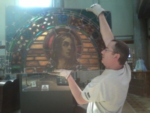 Pictured here holding a section of the St. John the Evangelist window is Colin Albig of Images in Glass which is located in Hamburg, New York. Images in Glass did the restoration and installation.