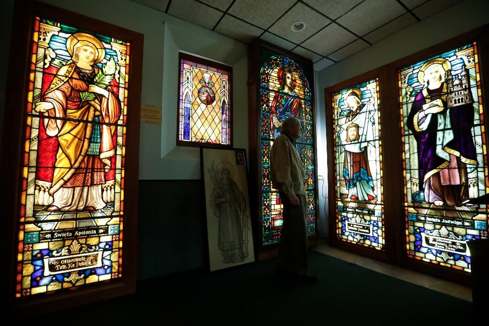 Bill Koch looks over some stained glass at the Buffalo Religious Arts Center, formerly St. Francis Xavier Church, on East Street in Buffalo. (Mark Mulville/Buffalo News)