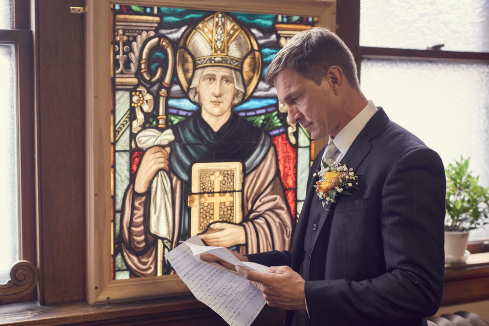 Austin Kennedy, Photographer.  Groom In Front Of Stained Glass Windows.