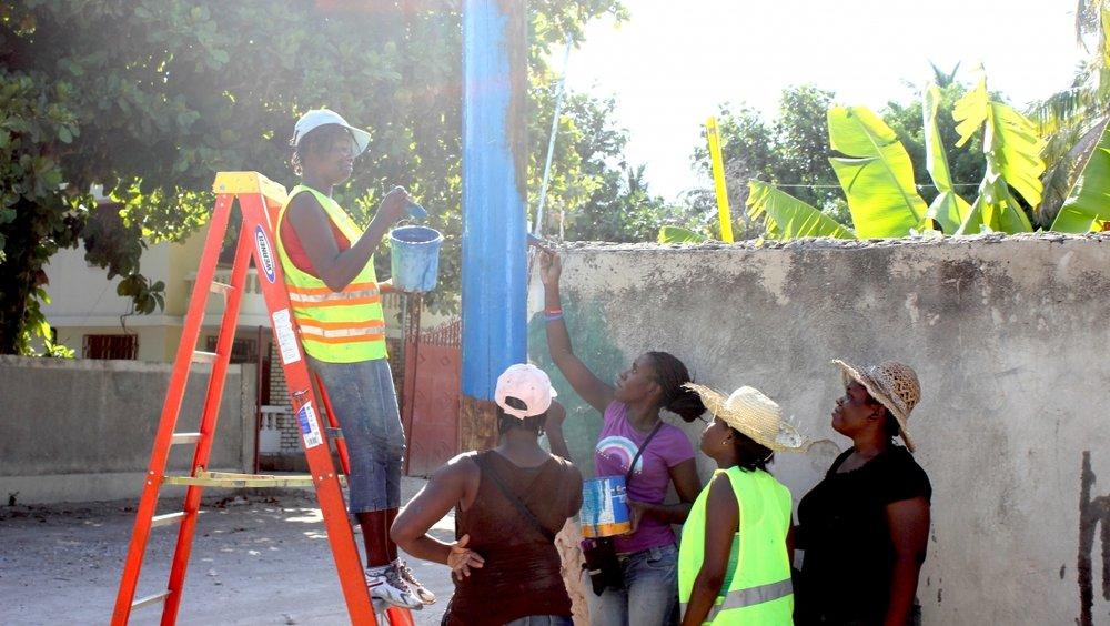 Photo Credit: Julia Pyper. Workers paint Sigora's utility poles the color of Haiti's flag.