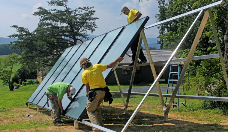 Sigora Solar workers install a solar thermal array at a residence on Miller Farm Road in Staunton. Shawn Cooke, Andy Bindea and Chris Sine position a 4-by-10 foot panel on the support frame. NORMAN CARTER