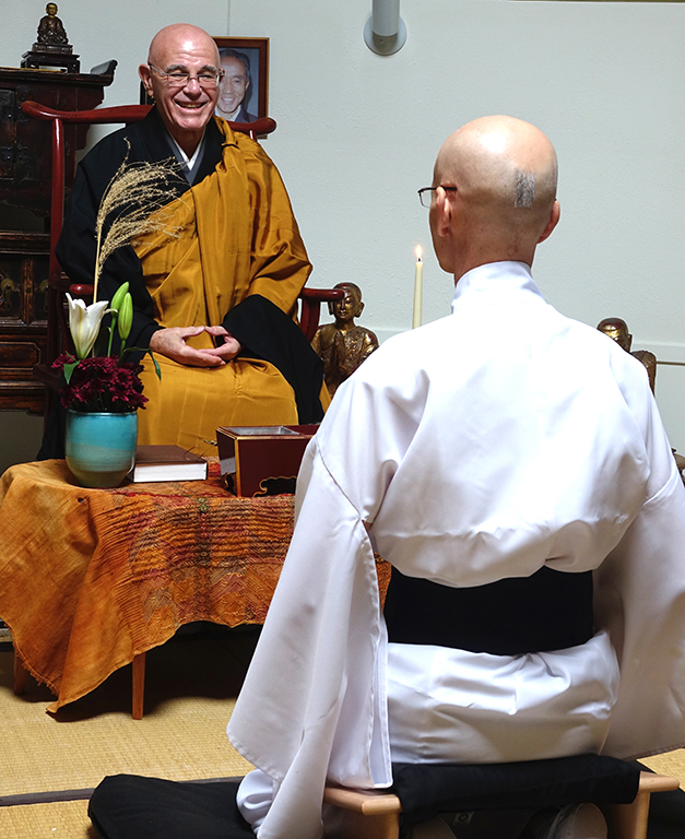Daishin Sensei smiles at Kikuu. A tuft of hair is left on Kikuu's head before it is shaven completely.
