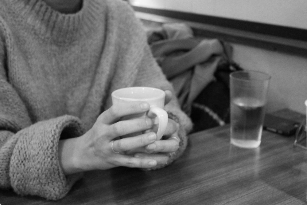 Un Jin grips her coffee cup.