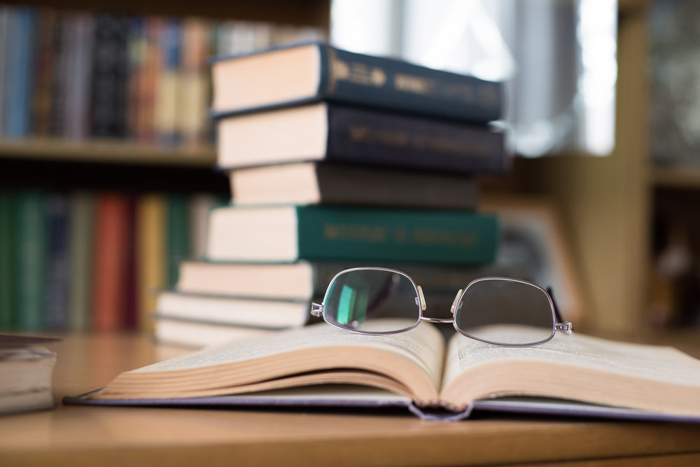 Library books stacked, open book with eyeglasses