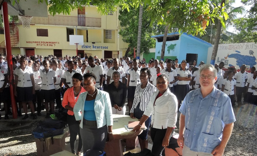 The Haitian Project President Deacon Patrick Moynihan (right) stands with Louverture Cleary School faculty and administration at an all-school morning prayer and meeting.