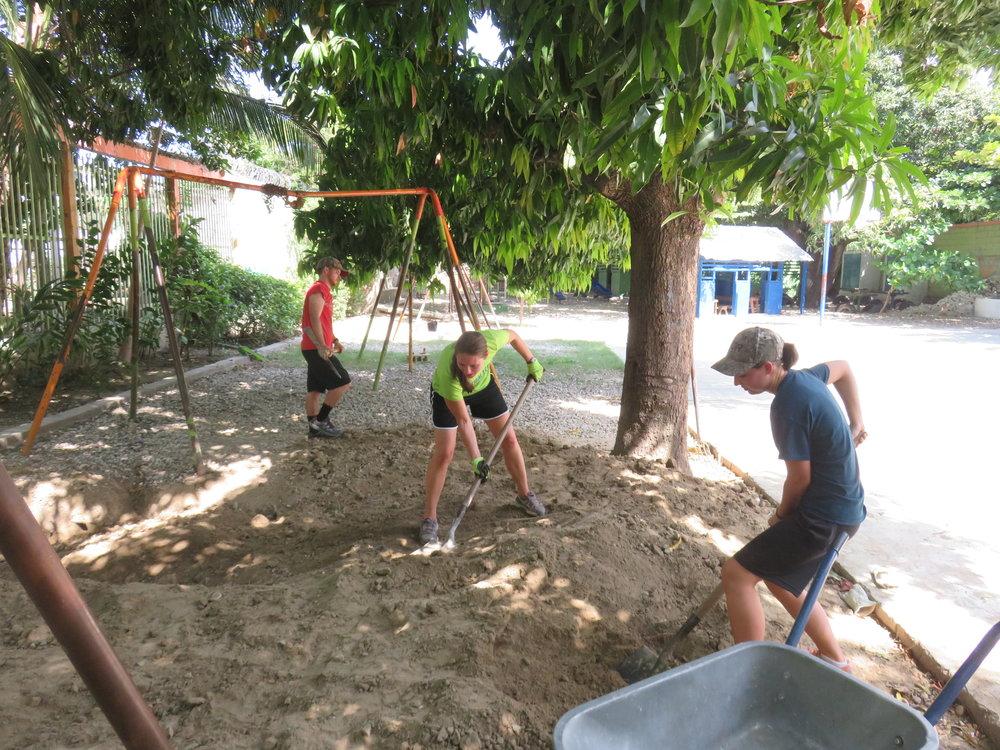 Volunteer Program Staff Connor Branham and Rachel Thelen and Volunteer Abigail Knapp work to level the playground.
