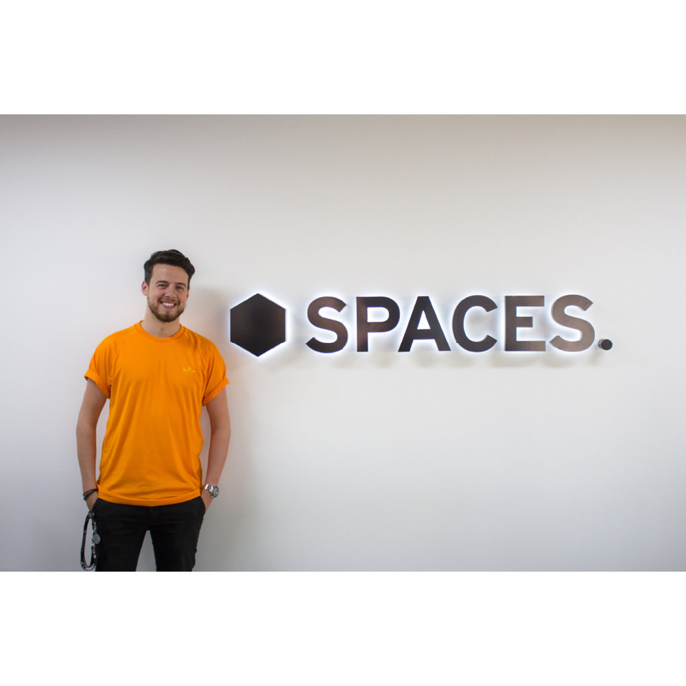 Enrico, the centre manager of Spaces, poses by the brandmark in our entrance hall