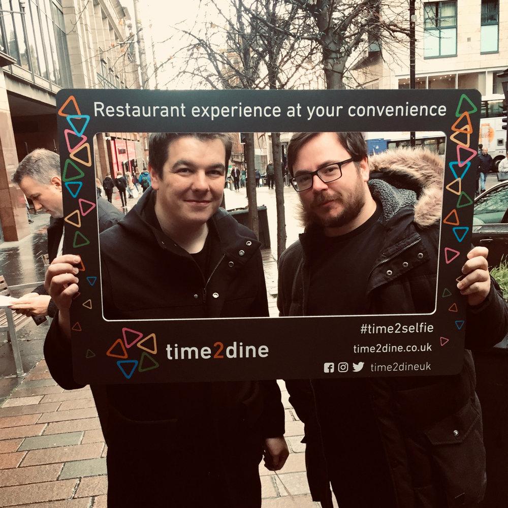 Chris & James pose in a selfie placard we designed for Time2Dine
