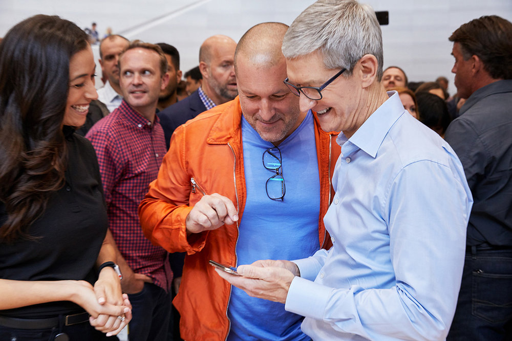 Jony Ive and Tim Cook (Apple's CEO) look at something on an iPhone