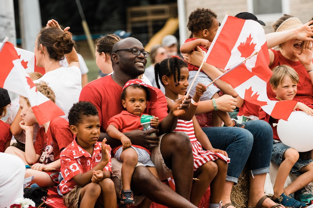 Smiling float riders wave at parade attendees at Canada's 150th celebration parade in Cambridge.