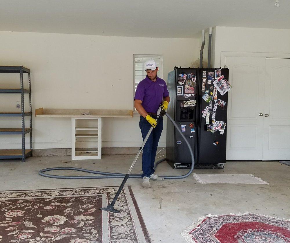 Christian deep cleaning an area rug.