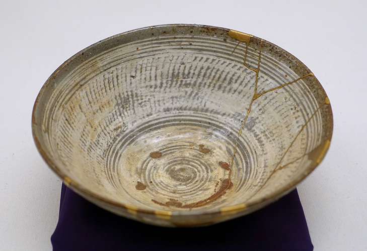 Repair work (right) on  Mishima ware   hakeme -type tea bowl with  kintsugi  gold lacquer, 16th century ( Ethnological Museum of Berlin ) By Daderot - Own work, CC0, https://commons.wikimedia.org/w/index.php?curid=45589849