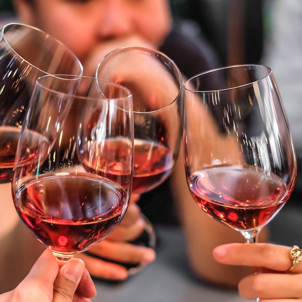 stock-photo-macro-shot-of-hands-raising-glasses-of-tasty-red-wine-in-a-social-gathering-245441047.jpg