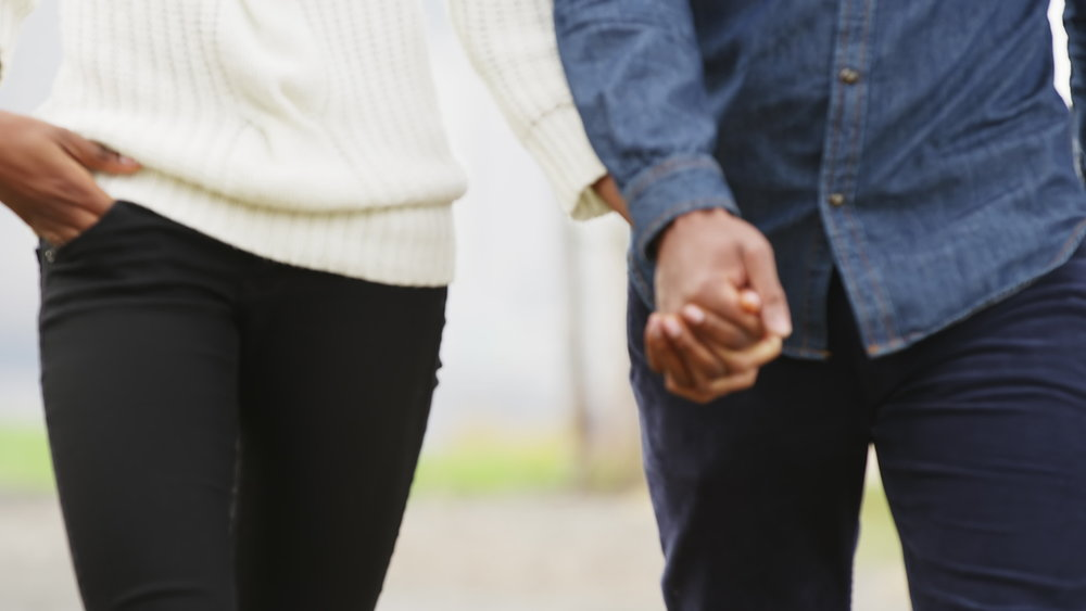 stock-footage-close-up-of-a-couple-holding-hands-while-walking-through-the-park-with-the-brooklyn-bridge-behind.jpg