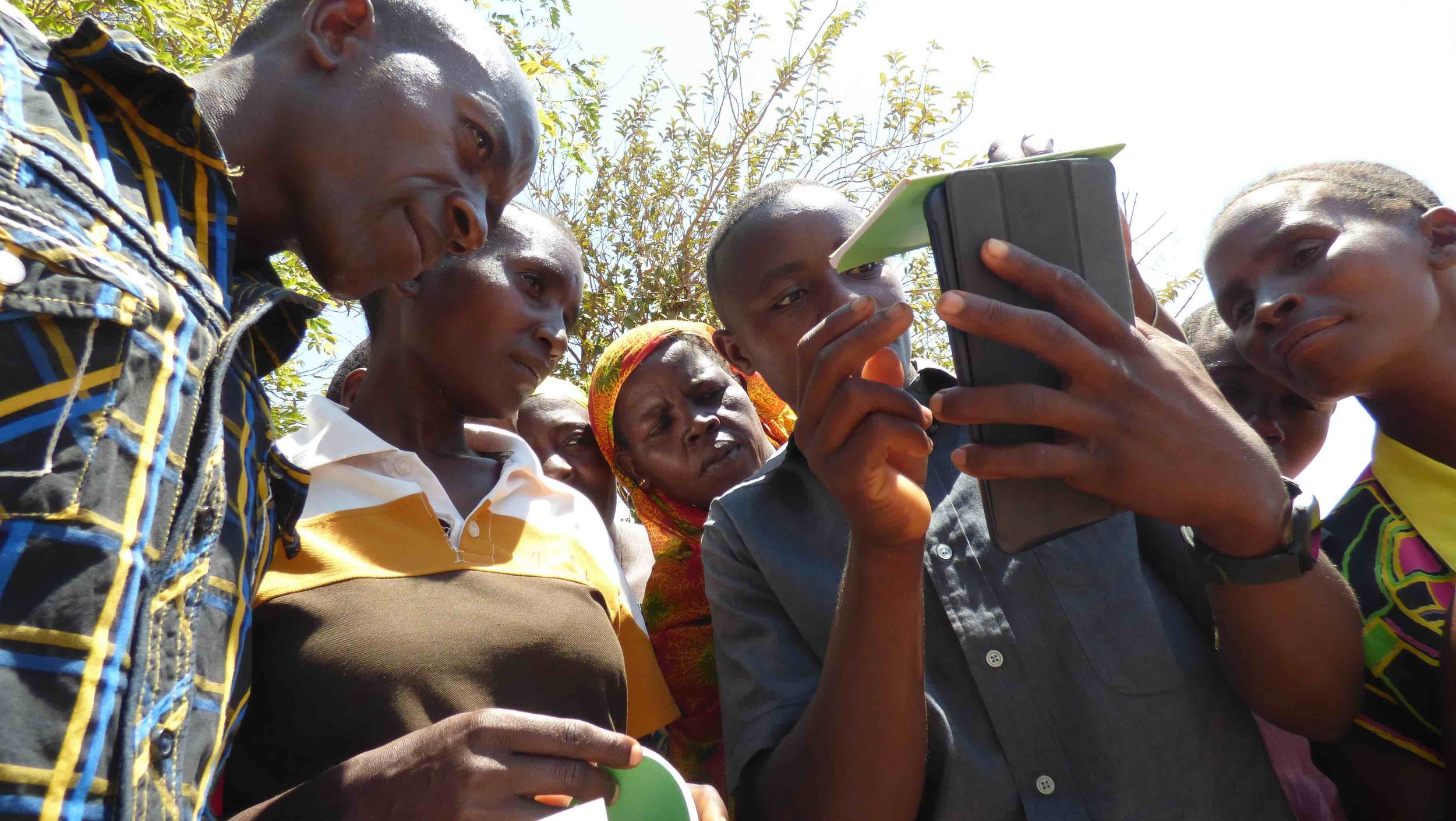 Tanzanian villagers with Self-Help Group facilitator and our savings and credit group Android mobile app (www.codeinnovation.com)