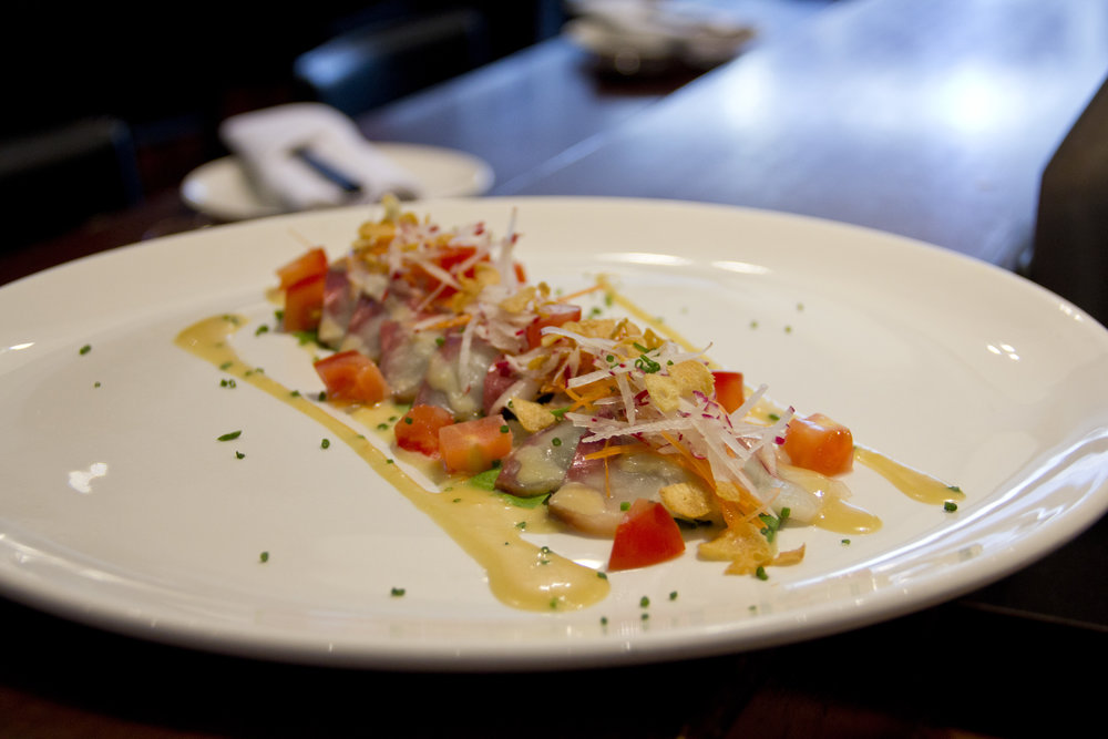 Tai (Snapper) Carpaccio served with a yuzu miso dressing, spring mix, thinly cut carrots, radish, and garlic chips.