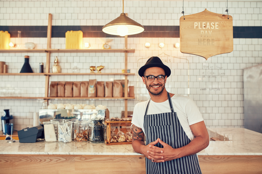makemoves-design-business-web-design-editorial-photography-male-barista-smiling-in-cafe.jpg