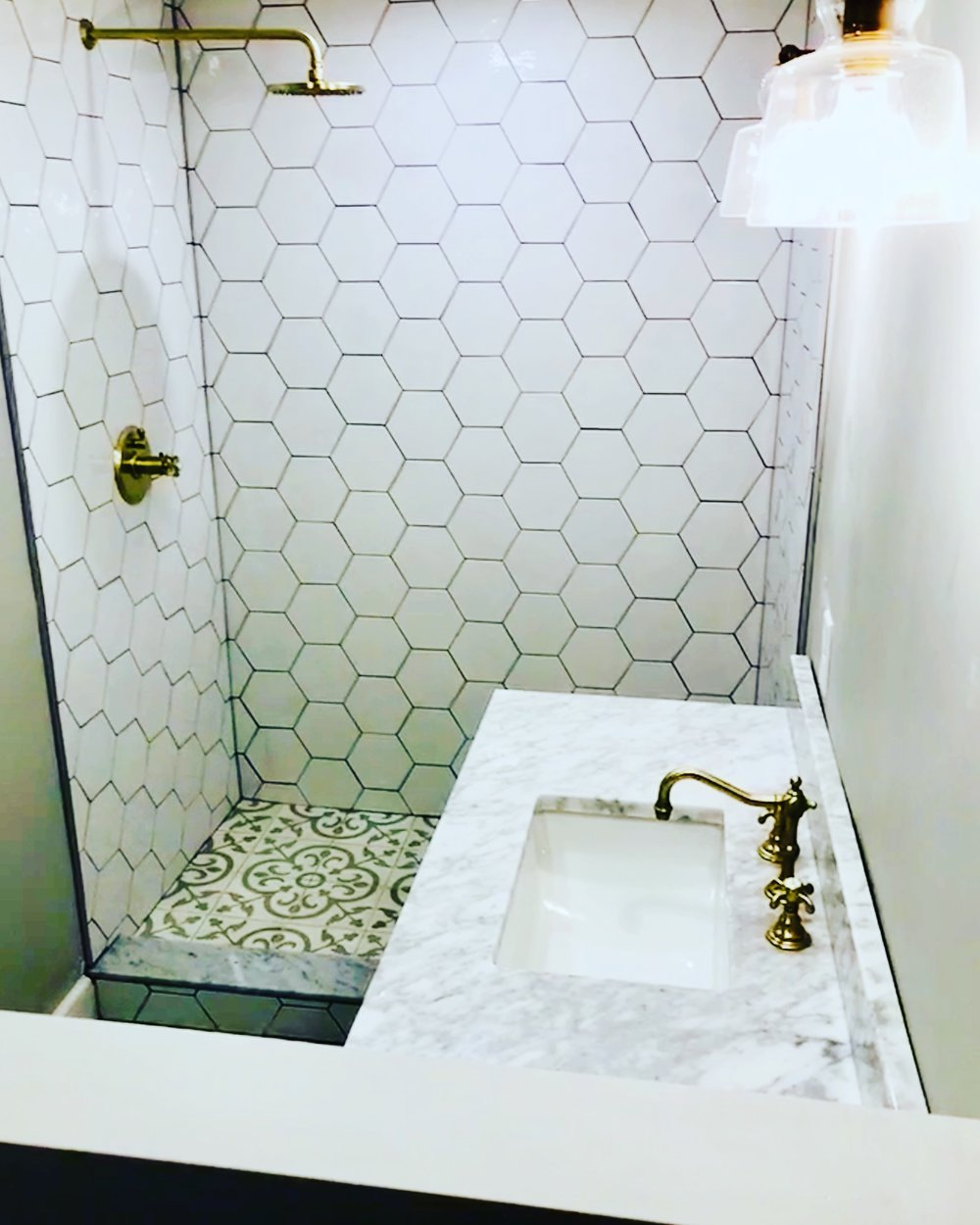Concrete floor tiles, hexagonal wall tiles in ceramic and brushed brass fixtures.