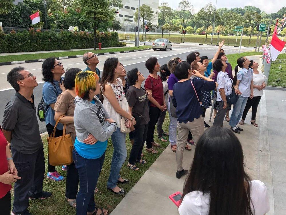 学员在听导览员介绍寺院及讲解三宝功德。
