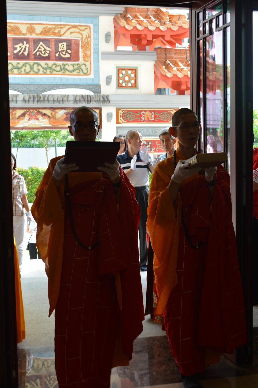 """接着,本思与本闻法师引领着信徒念诵""""南无本师释迦牟尼佛""""圣号,双手捧着《大藏经》,步伐不急不缓恭敬地把经函供奉在法坛上。"""