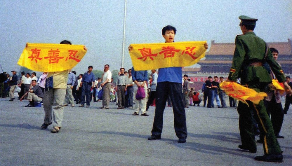 Falun Gong practitioners being illegally arrested by police in Beijing, China for holding up banners that read 'truthfulness, compassion, tolerance'.  Image credit: faluninfo.net