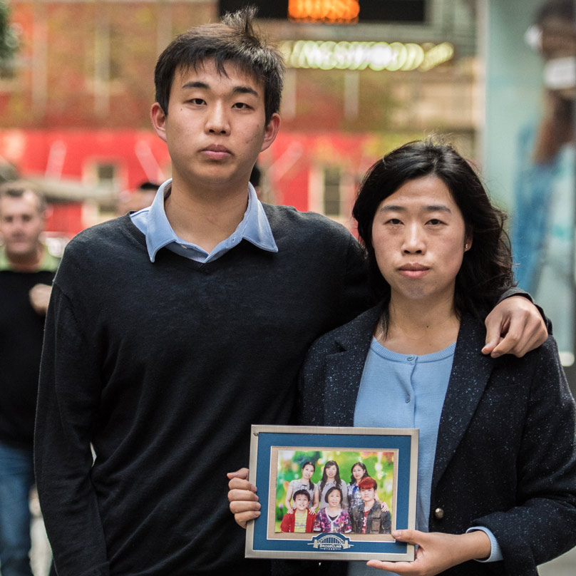 Falun Gong practitioners, Eric Jia and his Aunty Lorrita Liu, hold a photograph of family members still suffering persecution in China. Picture: Giovanni Portelli