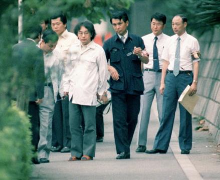 Miyazaki being lead down a road.