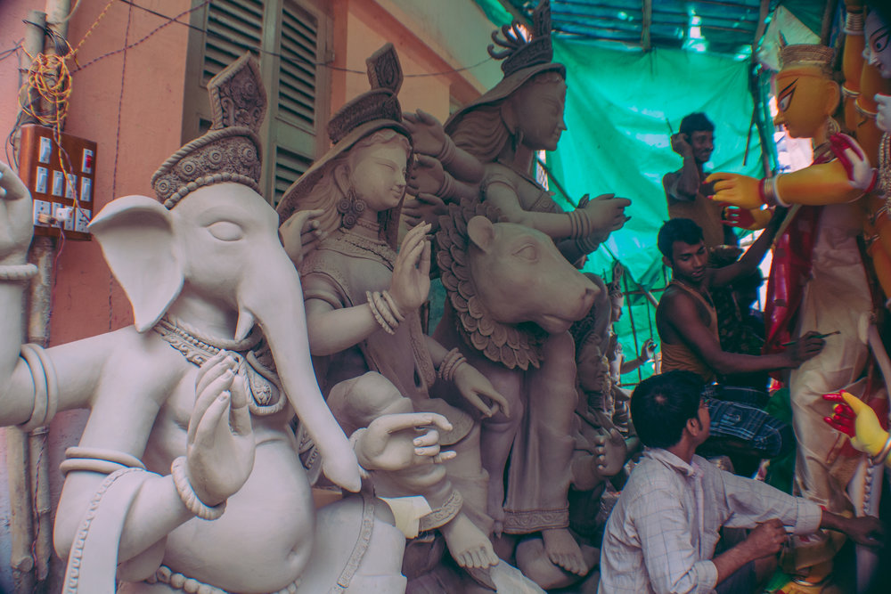 Artisans discuss the details of their craft while adding finishing touches to their sculptures, days before the start of Durga Puja.