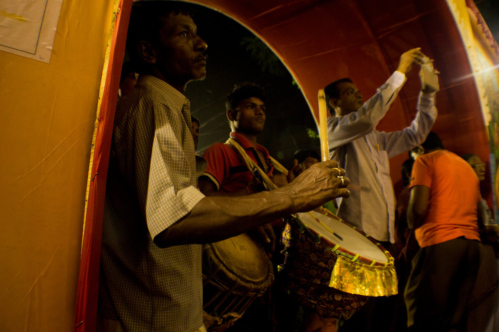 Shaped like a large barrel, a  dhak is an iconic instrument in Hindu rituals. Here, two  dhakis  add rhythm to the ceremonies honoring the goddess Durga.
