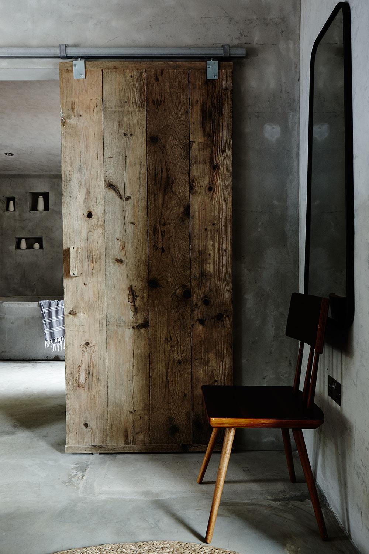 rustic_wood_door_concrete_bathroom.jpg