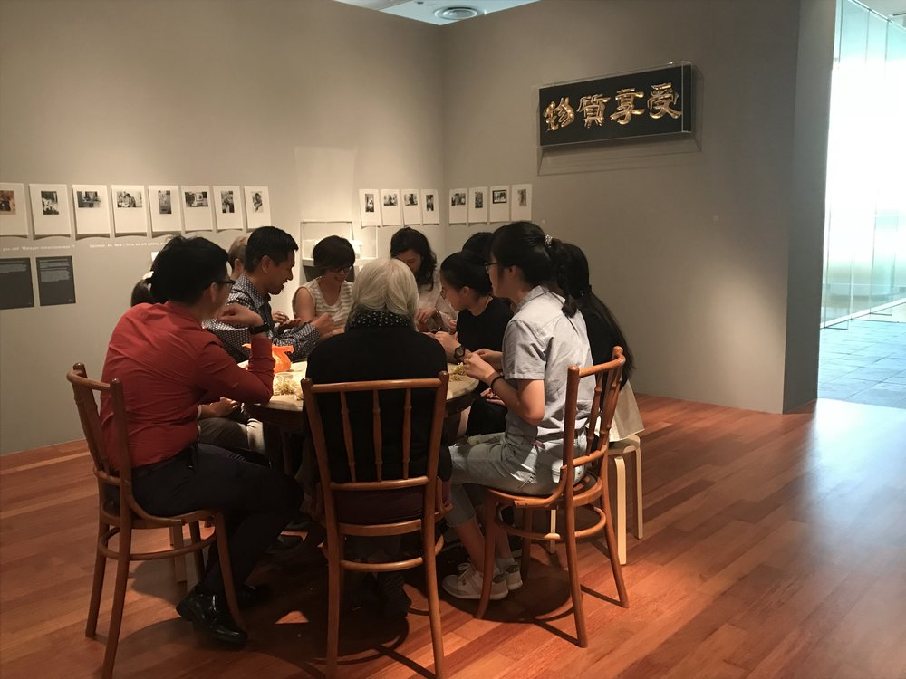 Artist Amanda Heng at  Let's Chat,  sitting at a table plucking beansprouts while chatting with a group of visitors.