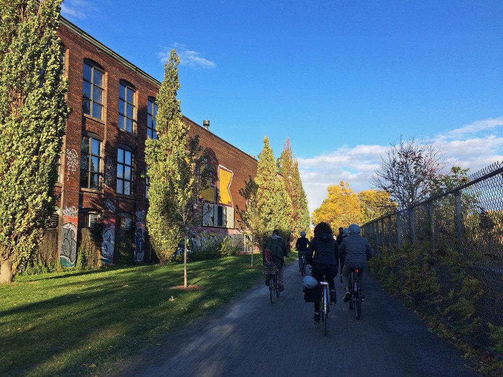 Biking along le réseau vert, an off-street greenway alongside railroad tracks in Montréal.