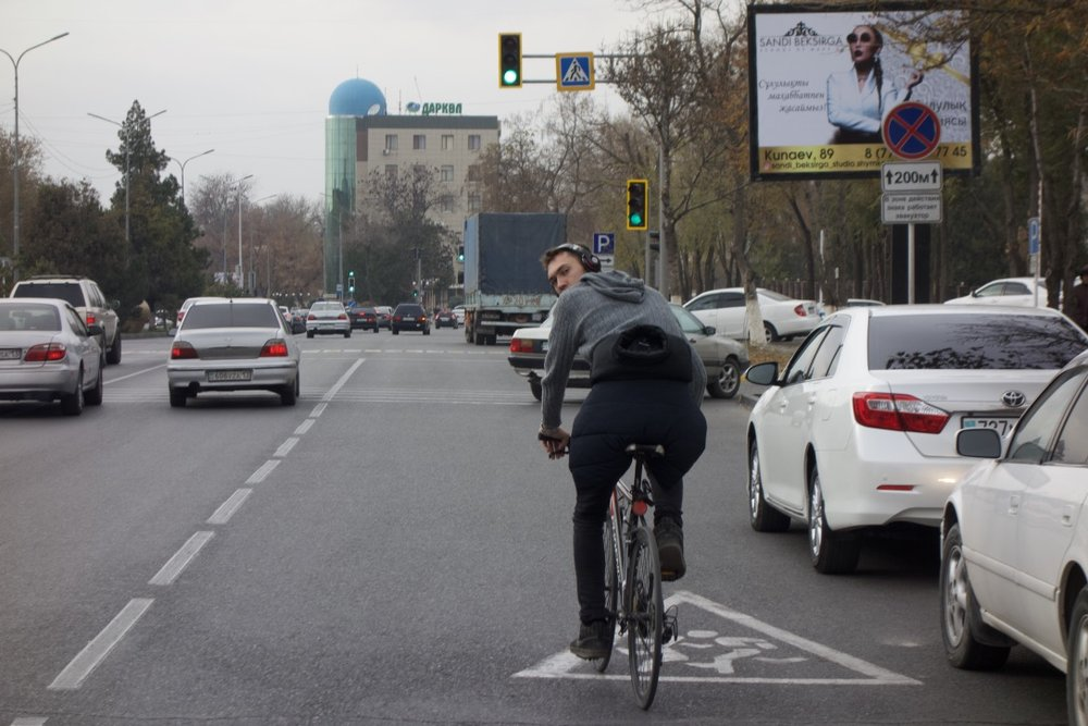 A local braves the wide, car-dominated streets of Shymkent.