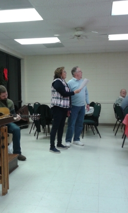 Praise Leader Britta and Pastor Ken Leads in Singing