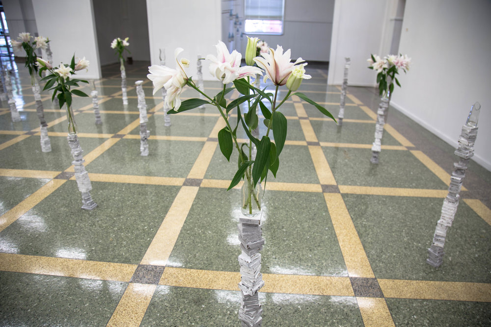 "Created at Southeastern Louisiana University in 2016 while acting as Visiting Artist. ""Missed Opportunities"" was a time based installation made to fit within their SLU's Contemporary Gallery space. Work evolved for 1 month after initial installation.        Materials: tar, gesso, wood, vases, flowers, time,"