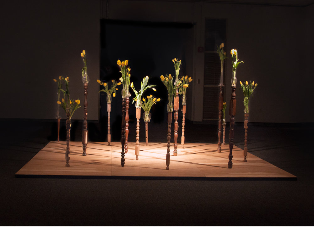 Connections Between  created in 2014 and installed in FSU's Museum of Fine Art for 31 days.    Materials: found objects, vases, yellow tulips, wood stage platform